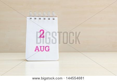 Closeup surface note book with pink 2 aug word in page on blurred brown wood desk and wood wall textured background with copy space under window light