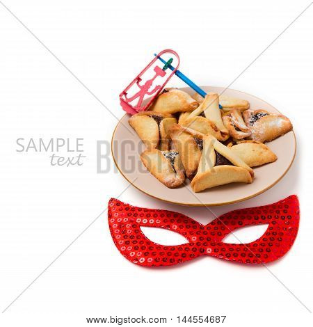 Hamantaschen cookies on plate and carnival mask on white background