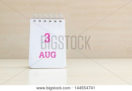 Closeup surface note book with pink 3 aug word in page on blurred brown wood desk and wood wall textured background with copy space under window light