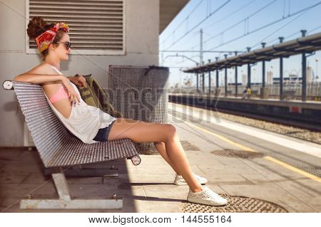 Young sexy long legs woman backpacker in tshirt and shorts waiting for train on platform on railway station. Travel concept.