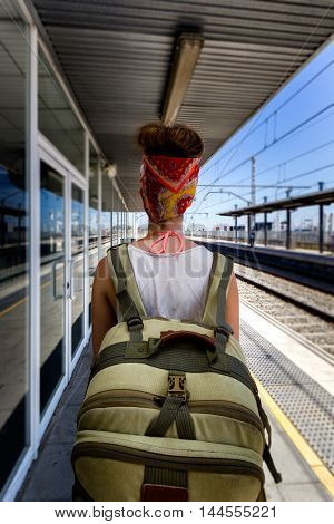 Young sexy woman backpacker waiting for train on platform on railway station. Travel concept.