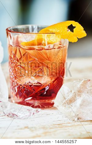Alcoholic Negroni cocktail consisting of vermouth, liqueur, gin and citrus peel in a glass beaker
