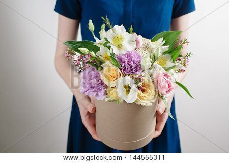 Work Florist, Bouquet In A Round Box. Smelling Flowers Holding Peach Roses In Hat Against The Plaste