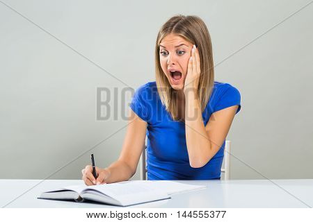 Beautiful female student is in panic beacuse she has got too much to study.