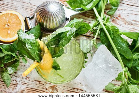 Top view of alcoholic cocktail Basil smash in a glass beaker and a piece of ice on a wooden table
