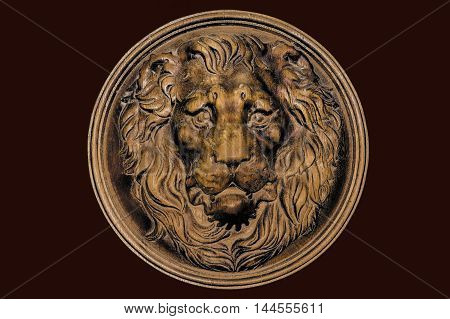 The face of a Lion carved from solid wood, isolated on deep red background