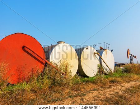 Metal Containers For Storage Of Crude Oil. A Small Private Oil Derrick Pumps Oil On The Field.