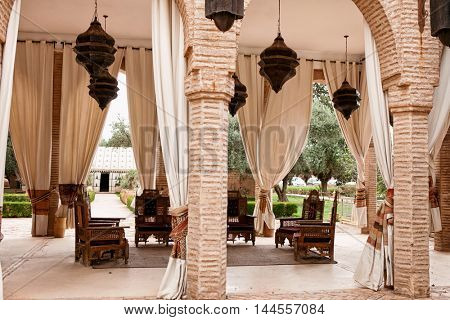 Traditional Moroccan living room. It consists of wooden pieces of furniture covered with a decorated fabric, Arabic shape design.