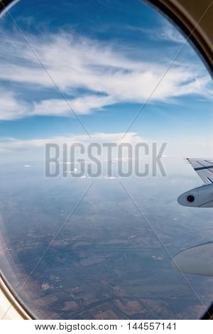 View of clouds and wing from airplane window