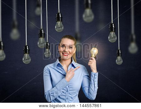 Smiling girl holding a light bulb shining above her head hanging light bulbs that do not light up