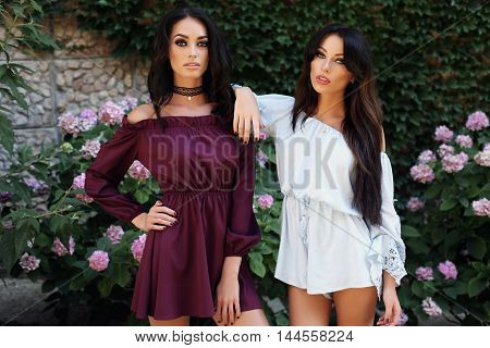 fashion outdoor photo of gorgeous women with dark hair in elegant dresses posing in summer garden
