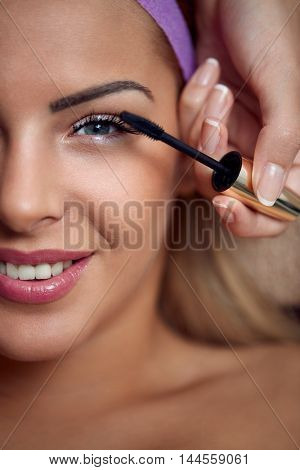 Mascara applying eyes make up by a beautician