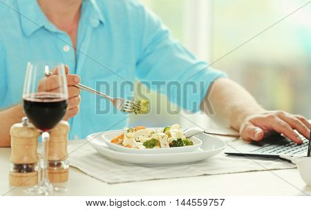 Man eating delicious pasta in restaurant