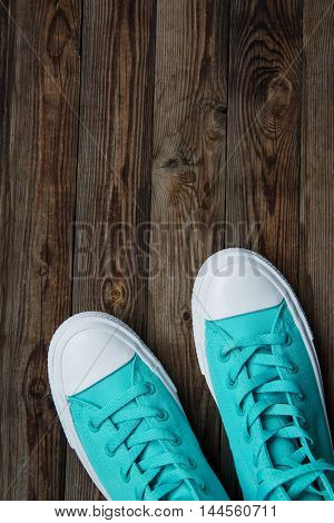 sneakers on empty wooden surface