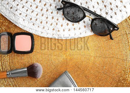 Set of decorative cosmetics and accessories on golden background