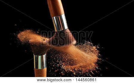 Make-up brush with beige powder explosion on black background
