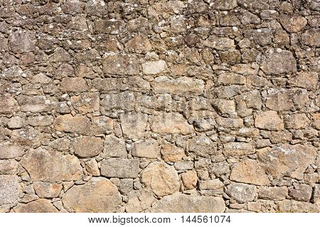 old stone wall made with irregular granite pieces