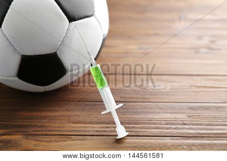 Syringe and soccer ball. Doping in sport concept