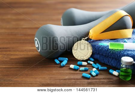 Syringe with pills, medal and dumbbells. Doping in sport concept