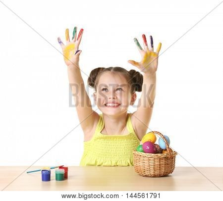 Cute girl with paint hands and Easter eggs on white background