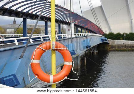 Glasgow Scotland Bridge over the river and orange lifebuoy.