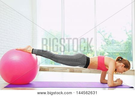 Girl with ball on light background