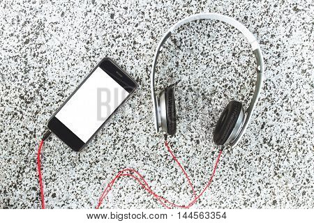 Smartphone with blank white screen lies nearby with headphones on gray marble background . The view from the top. Closeup. Listen to the music