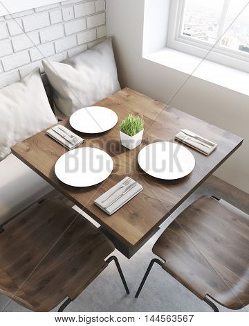 Square cafe table with plates. Sofa with pillows and chairs around it. Concept of eating out. 3d rendering. Top view