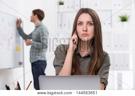 Man writing on whiteboard. Woman talking on her mobile phone. Bookshelves seen in background. Concept of day in office.