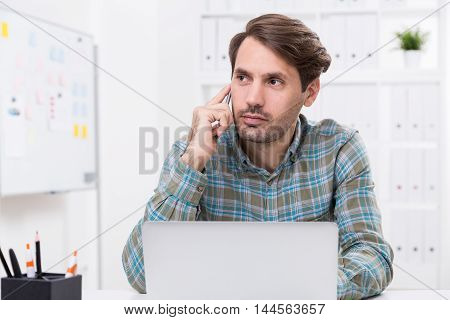 Businessman on phone in office. Whiteboard with stickers in background. Laptop on table. Concept of work routine