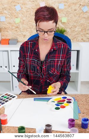 Woman painter in casual clothes is holding jar with yellow paint and getting ready to draw picture. Concept of art work