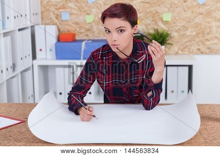 Woman in casual clothes holding glasses and looking to camera. Building blueprint lie on table in front of her. Concept of building and construction