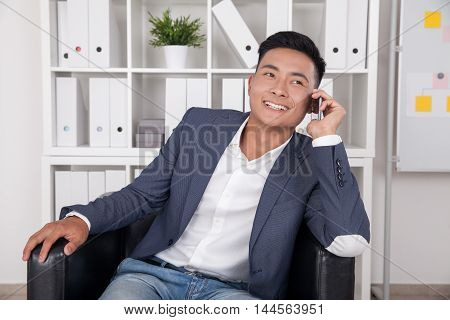 Asian Businessman Talking To His Wife On Phone