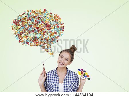 Girl with paintbrush and palette standing in light green background with speech bubble made of colorful icons. Concept of expressing oneself