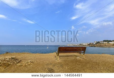 Lonely bench. Comfortable bench near the Mediterranean sea. Back view of bench near sea. Sea view wooden bench. Sea shore bench. Sea view bench