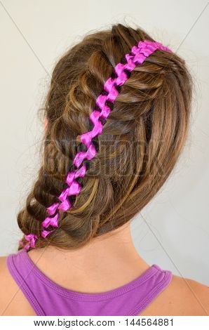 Hairstyle with long hair - braided purple ribbon in her hair, a young girl on a white background