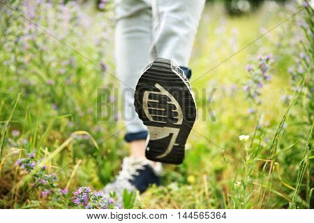 Woman feet in training shoes on grass background