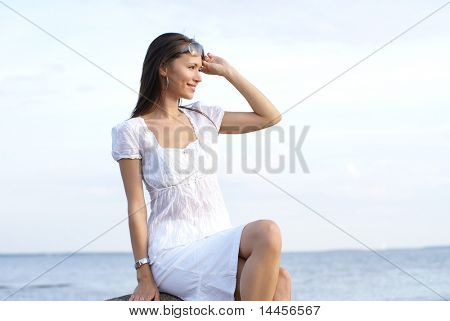Young sexy brunette sitting near the sea