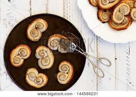 Palmier Biscuits Or French Pastry Made Of Puff Pastry And Cinnamon With Serving Tongs On Black Tray