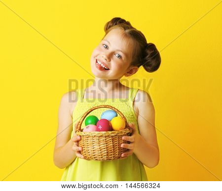 Cute girl with Easter eggs on yellow background