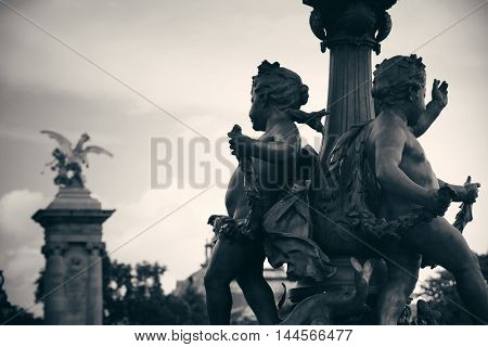 Vintage statue on Alexandre III bridge over River Seine in Paris, France.