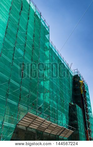 Modern building is under construction metal scaffolding with green network cover agaist blue sky.