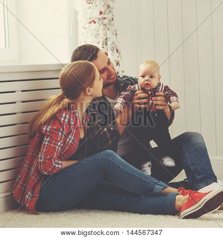 happy family mother and father playing with a baby at home