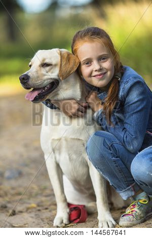 Little cute girl hugs dog (Labrador)