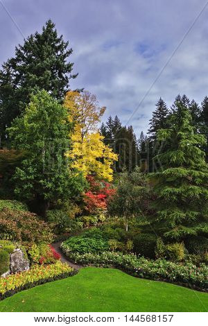 Flower beds of colorful flowers and walking paths for tourists. Butchart Gardens -  gardens on Vancouver Island. The world-famous masterpiece of park architecture