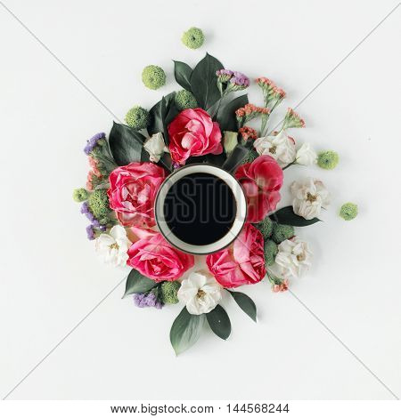 Colorful bright image made of leaves roses and petals with coffee cup on white. flat lay top view