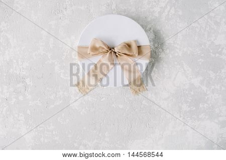 white gift cardboard box with brown bow on concrete background. flat lat top view