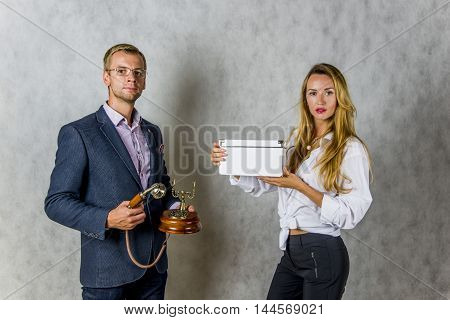 A man with a phone and a pretty girl with a box on a black phono
