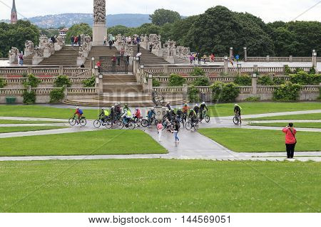 OSLO, NORWAY - JULY 1, 2016: A group of tourists are traveling on bicycles in the Vigeland Sculpture Park.