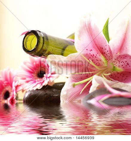 Bottle of massaging oil over spa background